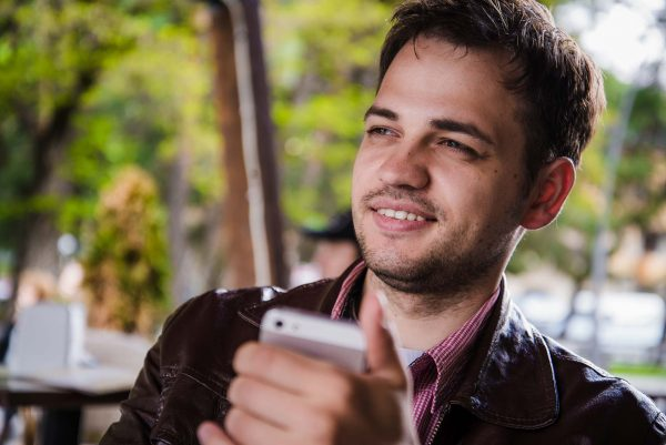 man with smartphone smiling